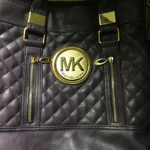 Purole quilted handbag featuring golden MK emblem